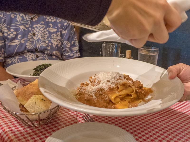ビーチウォークのアランチーノでパスタにチーズをかけてもらう様子